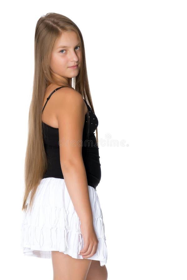 Ένα έφηβη σε μια κοντή άσπρη φούστα και μια μαύρη μπλούζα στοκ φωτογραφία με δικαίωμα ελεύθερης χρήσης