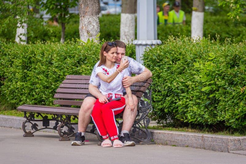 Ένα αγαπώντας ζεύγος κάθεται σε έναν πάγκο και κάνει selfies στοκ φωτογραφίες