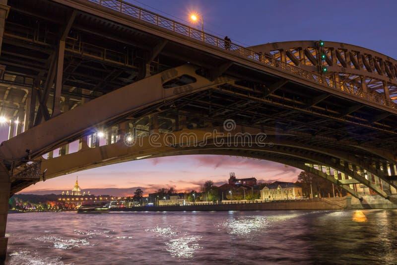 Ένα αγαπώντας ζεύγος στέκεται σε μια γέφυρα πέρα από τον ποταμό της πόλης βραδιού στοκ εικόνα