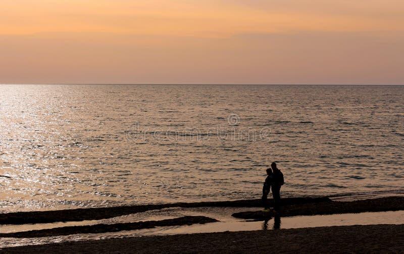 Ένα αγκαλιάζοντας ζεύγος σε ένα υπόβαθρο ηλιοβασιλέματος πέρα από τη θάλασσα στοκ φωτογραφία με δικαίωμα ελεύθερης χρήσης