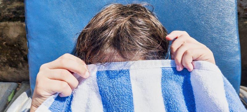 Ένα αγόρι εφήβων που ανατρέπεται, καλύπτει το πρόσωπό του με την πετσέτα παραλιών κινηματογράφηση σε πρώτο πλάνο του προσώπου και στοκ φωτογραφίες με δικαίωμα ελεύθερης χρήσης