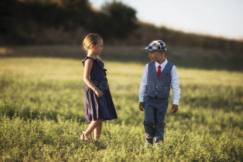 Ένα αγόρι και ένα κορίτσι στον τομέα στο φως ηλιοβασιλέματος στοκ εικόνα με δικαίωμα ελεύθερης χρήσης