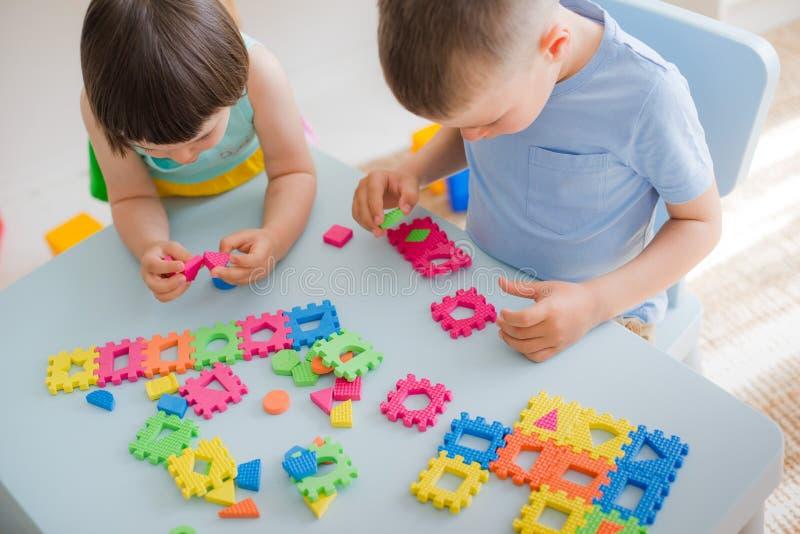 Ένα αγόρι και ένα κορίτσι συλλέγουν έναν μαλακό γρίφο στον πίνακα Ο αδελφός και η αδελφή έχουν το παιχνίδι διασκέδασης μαζί στο δ στοκ εικόνες με δικαίωμα ελεύθερης χρήσης