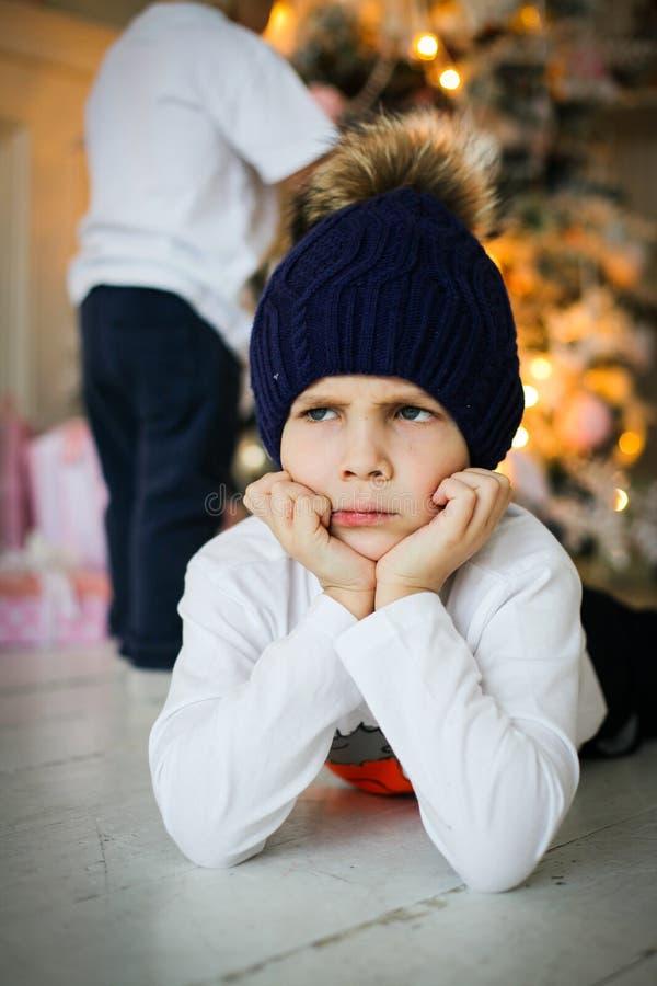 Ένα αγόρι κοντά στο δέντρο έλατου στη Παραμονή Πρωτοχρονιάς στοκ εικόνα