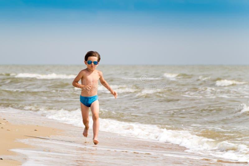 Ένα αγόρι με γυαλιά ηλίου τρέχει κατά μήκος της ακτής της θάλασσας με χρυσή άμμο Άλλα παιδιά στις θερινές διακοπές Φόντο αργιών στοκ εικόνες