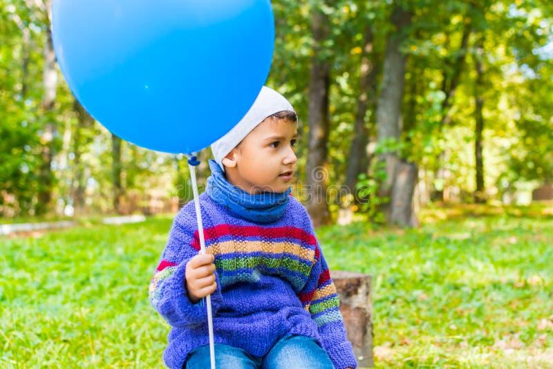Ένα αγόρι με μια συνεδρίαση μπαλονιών σε ένα κολόβωμα στο υπόβαθρο του δάσους στοκ εικόνα με δικαίωμα ελεύθερης χρήσης