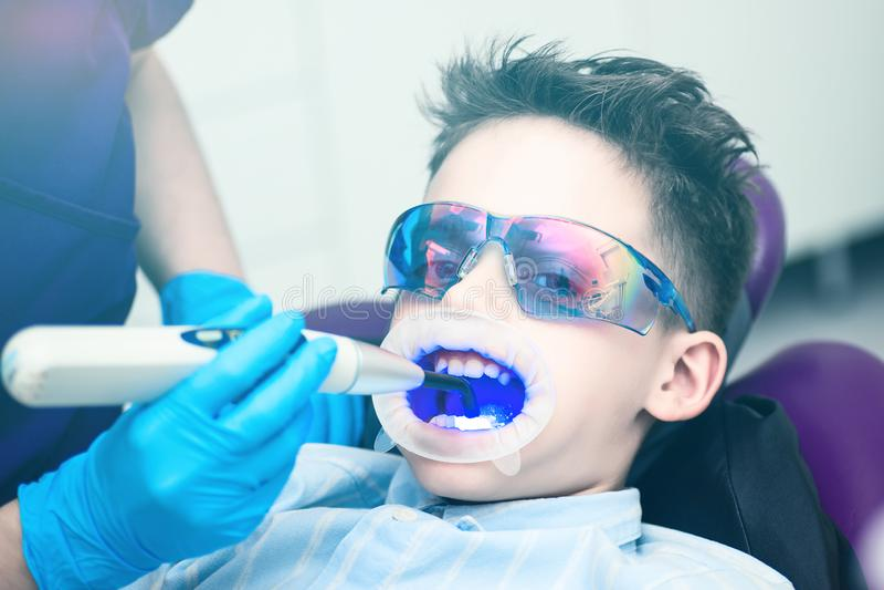 Ένα αγόρι με τα προστατευτικά δίοπτρα στην οδοντική καρέκλα Κατευθυνόμενος στόμα λαμπτήρας lightpolymerization με το μπλε φως για στοκ εικόνες με δικαίωμα ελεύθερης χρήσης
