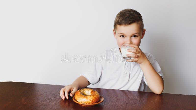 Ένα αγόρι, μια κουζίνα, bagel και ένα γάλα πρόγευμα υγιές στοκ φωτογραφία
