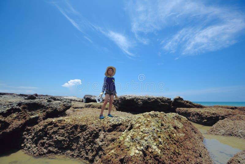 Ένα αγόρι παίζει την εξερεύνηση στους βράχους παραλιών στοκ εικόνες με δικαίωμα ελεύθερης χρήσης