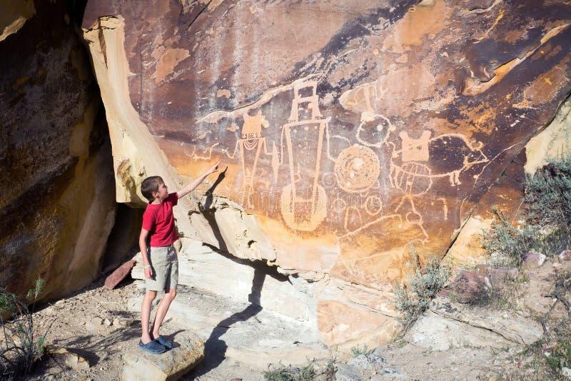 Ένα αγόρι παρουσιάζει χέρι του στον τοίχο με petroglyphs Δεινόσαυρος Nati στοκ εικόνες με δικαίωμα ελεύθερης χρήσης