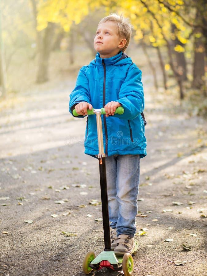 Ένα αγόρι που οδηγά ένα μηχανικό δίκυκλο στο πάρκο φθινοπώρου στοκ εικόνα