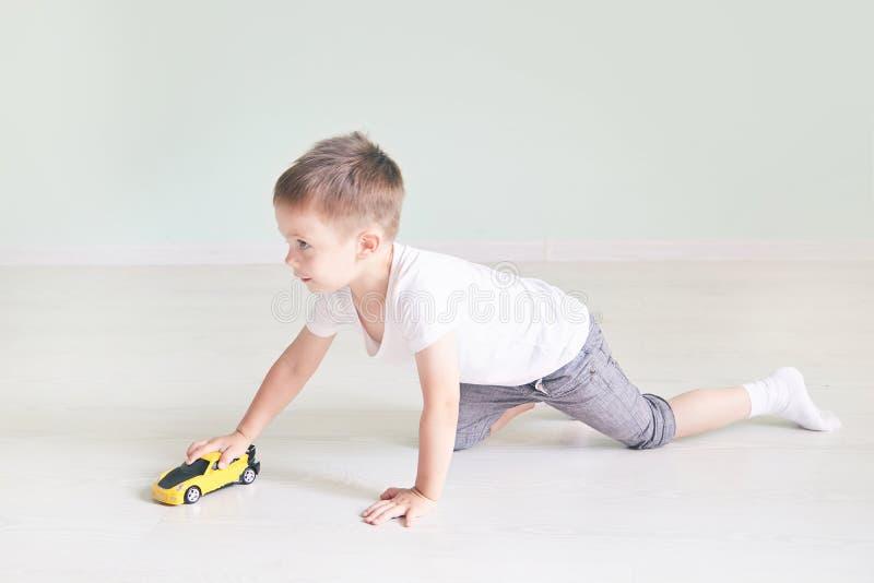 Ένα αγόρι που παίζει με ένα αυτοκίνητο μακρινό στοκ εικόνα