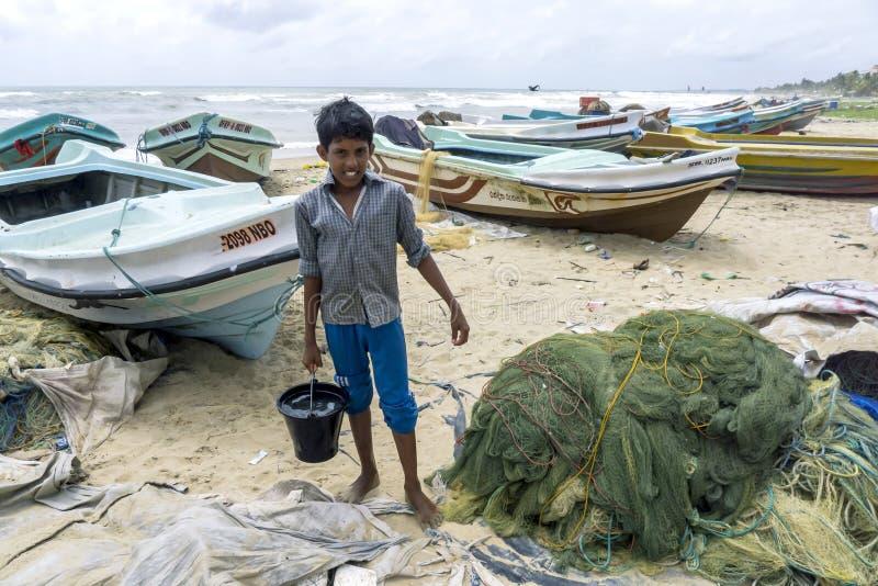 Ένα αγόρι που συλλέγει το νερό στην παραλία μπροστά από ένα ψαροχώρι σε Negombo, Σρι Λάνκα στοκ φωτογραφίες με δικαίωμα ελεύθερης χρήσης
