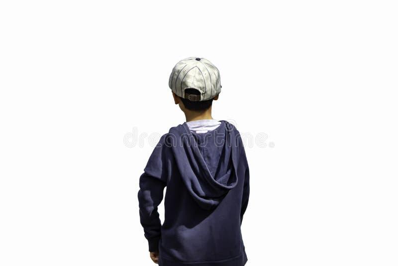 Ένα αγόρι που φορά ένα χειμερινά σακάκι και ένα καπέλο που στέκονται στην άσπρη πλάτη στοκ εικόνα με δικαίωμα ελεύθερης χρήσης