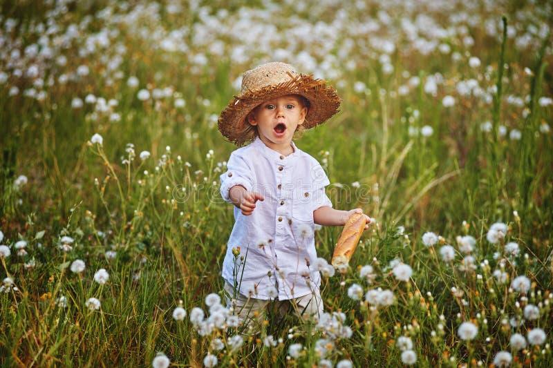 Ένα αγόρι σε ένα καπέλο αχύρου με μια φραντζόλα του γαλλικού ψωμιού στοκ φωτογραφίες με δικαίωμα ελεύθερης χρήσης