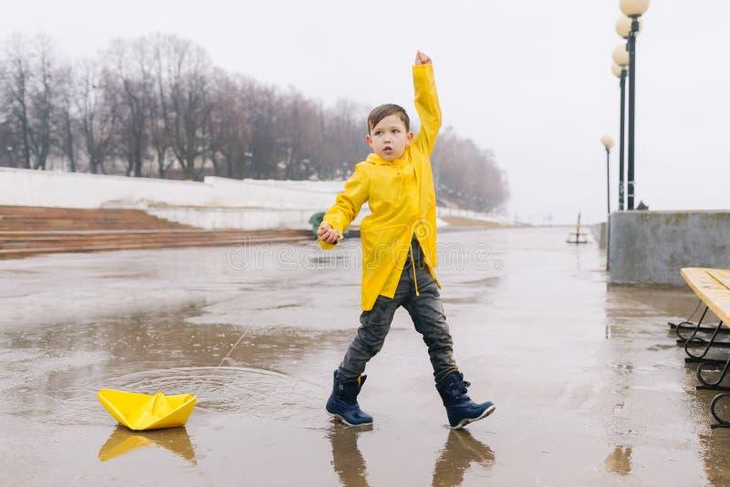 Ένα αγόρι σε ένα κίτρινο αδιάβροχο παίζει μια μεγάλη βάρκα εγγράφου σε μια λακκούβα στοκ εικόνες