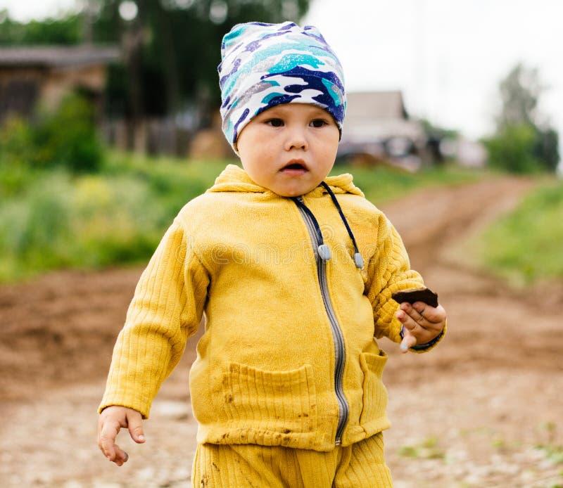 Ένα αγόρι σε ένα κίτρινο κοστούμι που κρατά μια πέτρα διαθέσιμη στοκ εικόνα