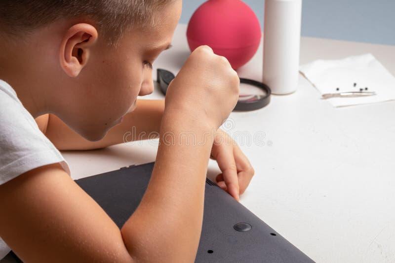 Ένα αγόρι 10 χρονών ταξινομεί ένα lap-top για τον καθαρισμό και τη συντήρηση r Κατσαβίδια, κύλινδρος εκκαθαρίσεων, ενίσχυση στοκ φωτογραφία με δικαίωμα ελεύθερης χρήσης