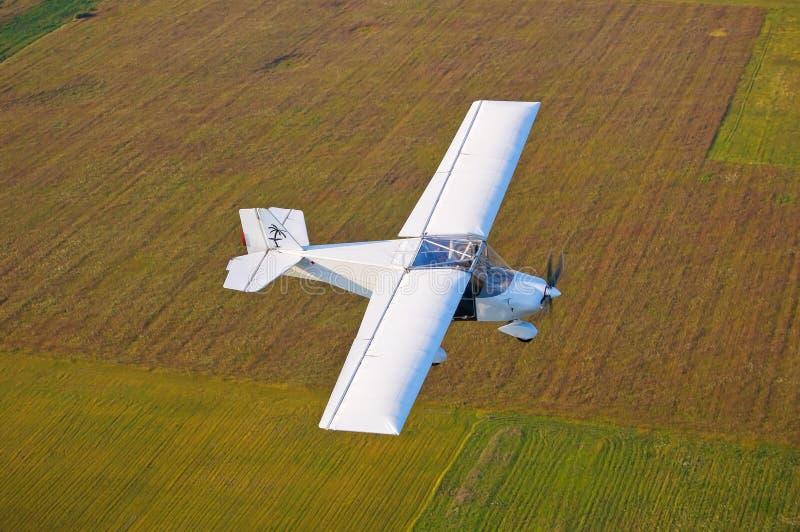 Ένα αεροπλάνο που πετά επάνω από τα πεδία στοκ εικόνες