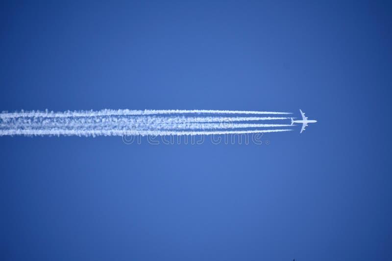 Ένα αεροπλάνο αεριωθούμενων αεροπλάνων που πετά από πάνω αφήνει τέσσερα ίχνη συμπύκνωσης ενάντια σε έναν ζωηρό, μπλε ουρανός στοκ φωτογραφίες με δικαίωμα ελεύθερης χρήσης