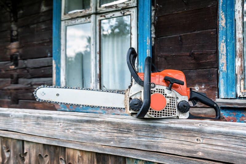 Ένα αλυσιδοπρίονο κοντά στο ξύλινο σπίτι στοκ εικόνες