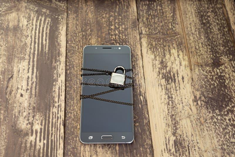 Ένα αλυσοδεμένο smartphone - έννοια προστασίας δεδομένων στοκ φωτογραφία