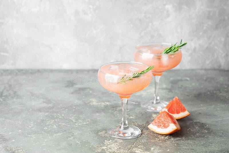 Ένα αναζωογονώντας θερινό κοκτέιλ του δεντρολιβάνου γκρέιπφρουτ και του χυμού πάγου στο κομψό goblets γυαλιού γκρίζο συγκεκριμένο στοκ εικόνες