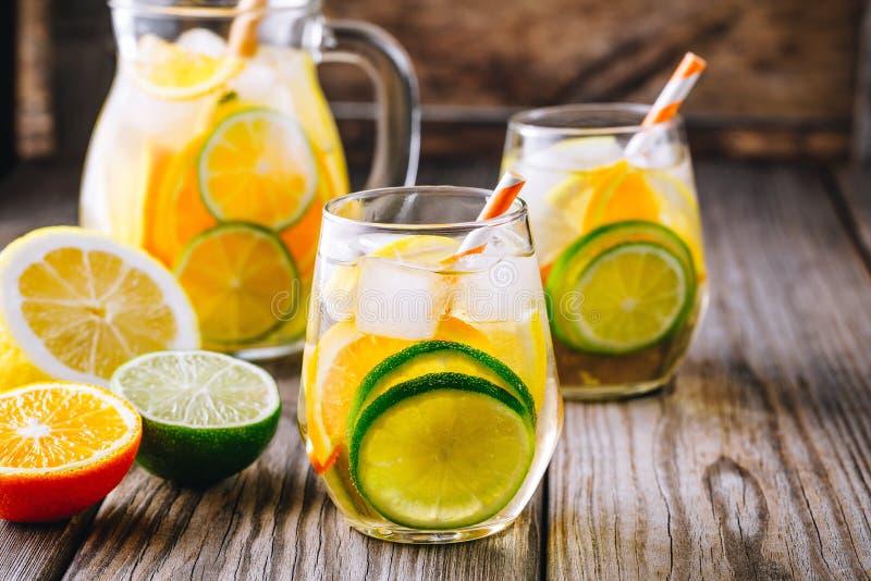 Ένα αναζωογονώντας θερινό ice-cold ποτό Άσπρο sangria κρασιού στο γυαλί με τον ασβέστη, το λεμόνι και το πορτοκάλι στοκ εικόνα