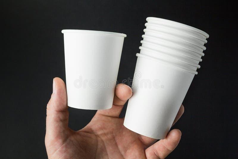 Ένα ανθρώπινο χέρι κρατά τα πρότυπα των φλυτζανιών για τον καφέ, το τσάι, τη σόδα και το χυμό σε ένα μαύρο υπόβαθρο στοκ εικόνες