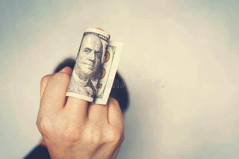 Ένα ανθρώπινο χέρι κρατά το λογαριασμό εκατό δολαρίων και παρουσιάζει μέσο δάχτυλό του συγχρόνως στοκ εικόνα
