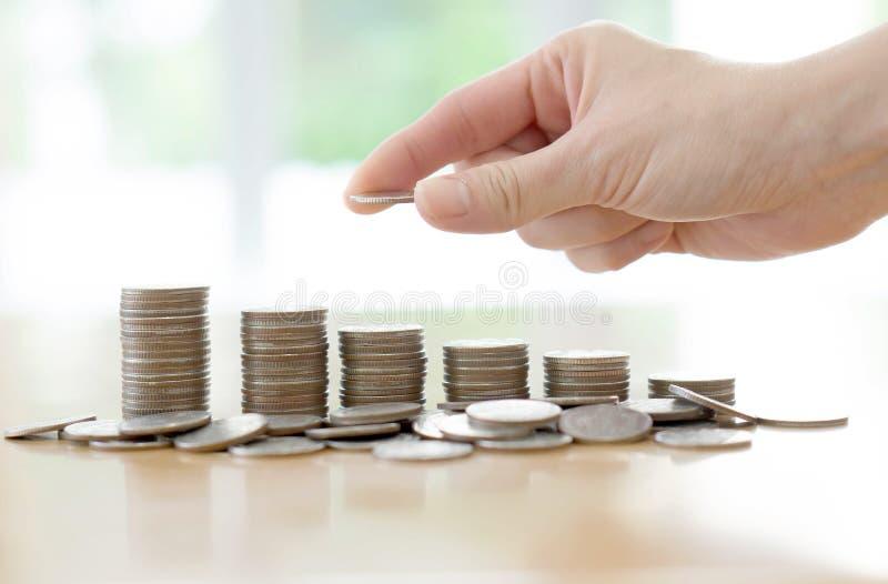 Ένα ανθρώπινο χέρι χεριών που βάζει το νόμισμα στα χρήματα, επιχειρησιακές ιδέες στοκ φωτογραφία