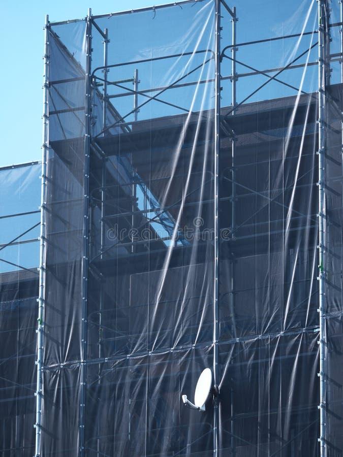 Ένα απομονωμένο δορυφορικό πιάτο στο ικρίωμα του εξωτερικού τοίχου που επισκευάζει την εργασία ενός σπιτιού διαμερισμάτων στοκ εικόνες με δικαίωμα ελεύθερης χρήσης