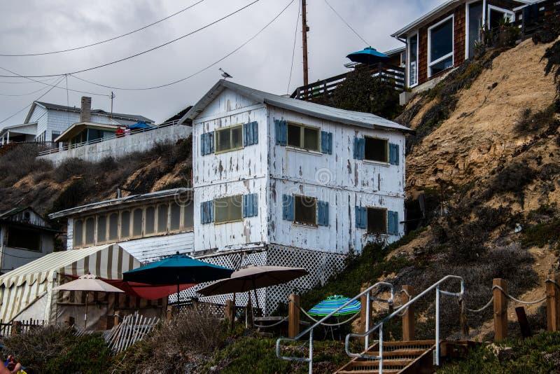 Ένα από διάφορα σπίτια στην ερείπωση που αποκαθίστανται κατά μήκος της παραλίας και της ακτής του όρμου κρυστάλλου όπως βλέπουν κ στοκ φωτογραφία