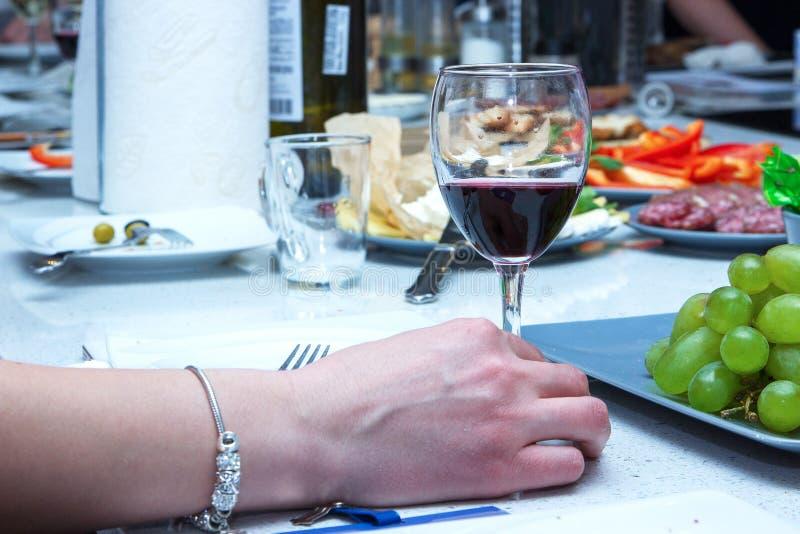 Ένα από τα κορίτσια που τα φλάουτα με το λαμπιρίζοντας κρασί Τα κορίτσια δίνουν με τη λαβή βραχιολιών ένα ποτήρι του κόκκινου κρα στοκ εικόνες