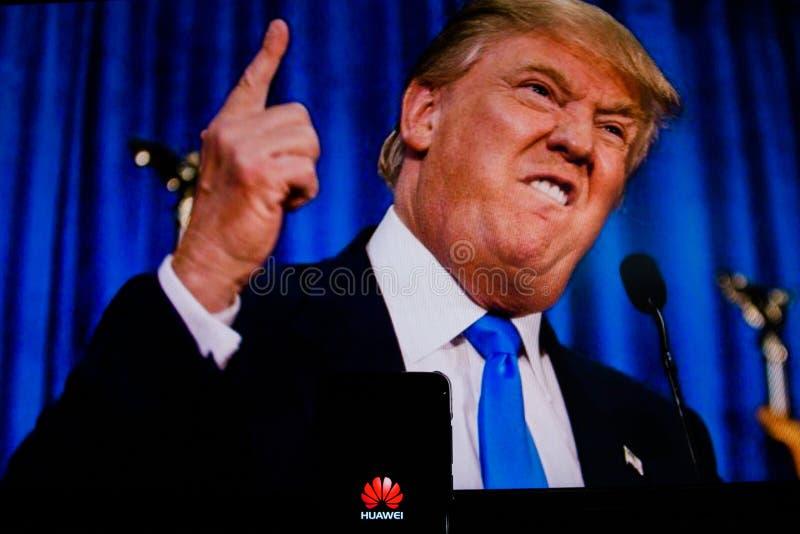 Ένα αρρενωπός-smartphone που παρουσιάζει λογότυπο Huawei μπροστά από την εικόνα του Ντόναλντ Τραμπ στοκ φωτογραφία με δικαίωμα ελεύθερης χρήσης
