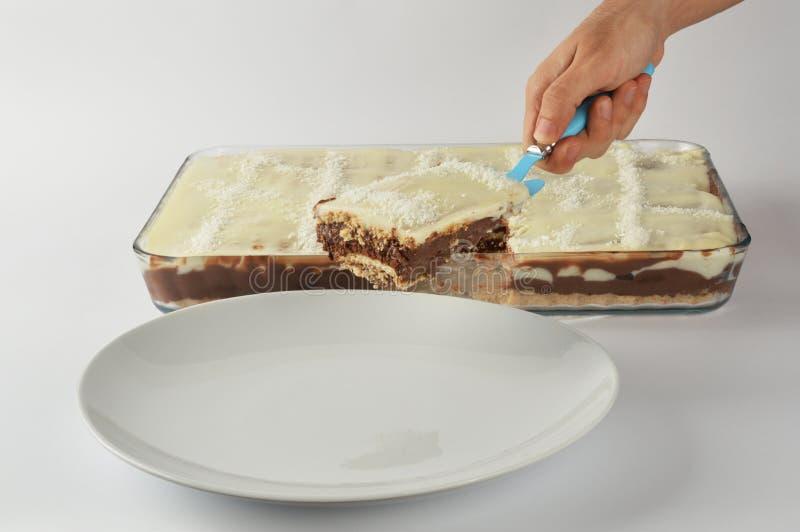 Ένα αρσενικό εξυπηρετώντας κομμάτι χεριών του σπιτικού κέικ στοκ φωτογραφία