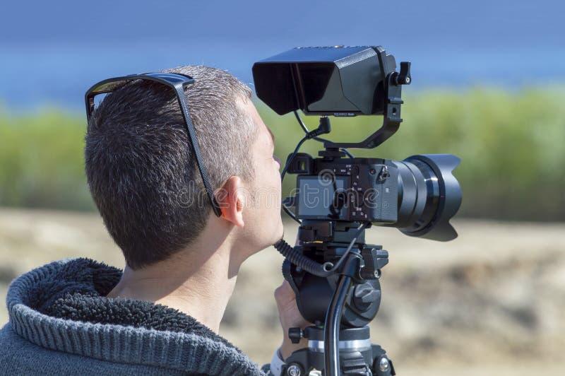 Ένα αρσενικό καμεραμάν κάνει έναν κινηματογράφο υπαίθρια στη φύση στοκ φωτογραφίες με δικαίωμα ελεύθερης χρήσης