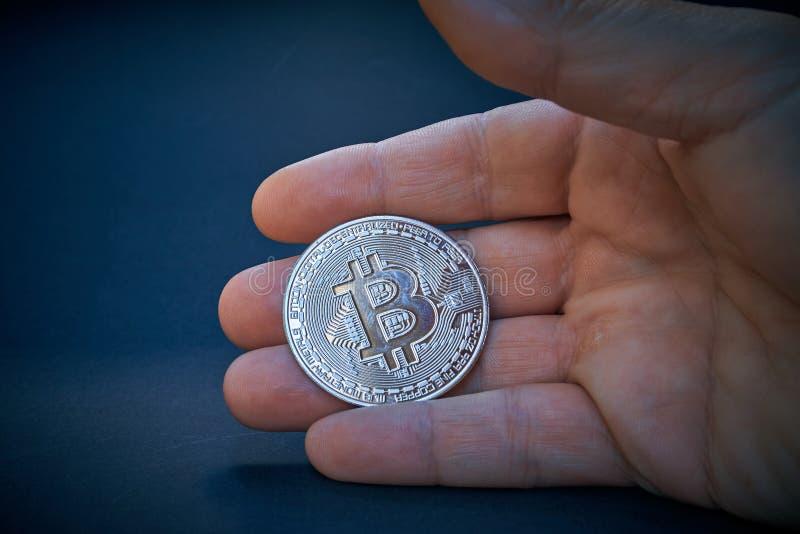 Ένα ασημένιο Bitcoin είναι στο ανοικτό χέρι Το νόμισμα λάμπει και απεικονίζει το φως Το υπόβαθρο είναι σκοτεινό και αφηρημένο Το  στοκ φωτογραφίες
