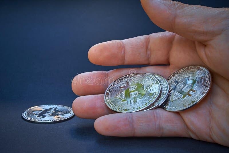 Ένα ασημένιο Bitcoin είναι στο ανοικτό χέρι Το νόμισμα λάμπει και απεικονίζει το φως Το υπόβαθρο είναι σκοτεινό και αφηρημένο Το  στοκ φωτογραφίες με δικαίωμα ελεύθερης χρήσης