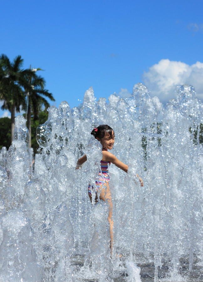 Ένα ασιατικό κορίτσι που παίζει από την πηγή ύδατος στοκ εικόνες