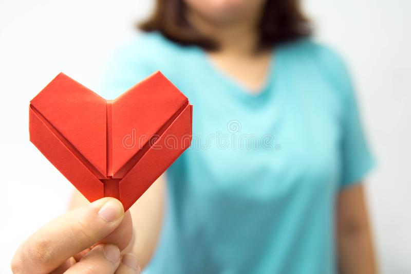 Ένα ασιατικό origami καρδιών εκμετάλλευσης γυναικών μπροστά από τη θωρακική Α γυναίκα της που δίνει το κόκκινο έγγραφο καρδιών σε στοκ εικόνα
