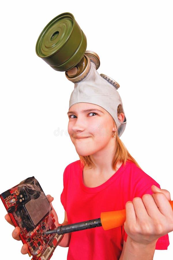 Ένα αστείο, μια παρωδία Το κορίτσι στη μάσκα αερίου θέλει να καψει μια σπασμένη τηλεοπτική κάρτα συγκολλώντας σιδήρου στοκ εικόνα