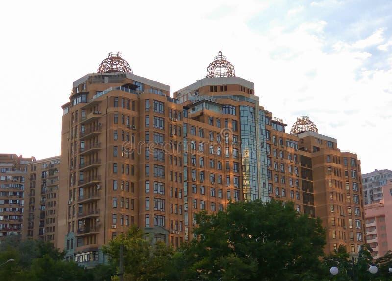 Ένα ασυνήθιστο ρόδινο multi-storey κτήριο ή ένα σπίτι με το μπλε γυαλί Γεωμετρικό σχέδιο ενός multi-storey ρόδινου κτηρίου στοκ φωτογραφία