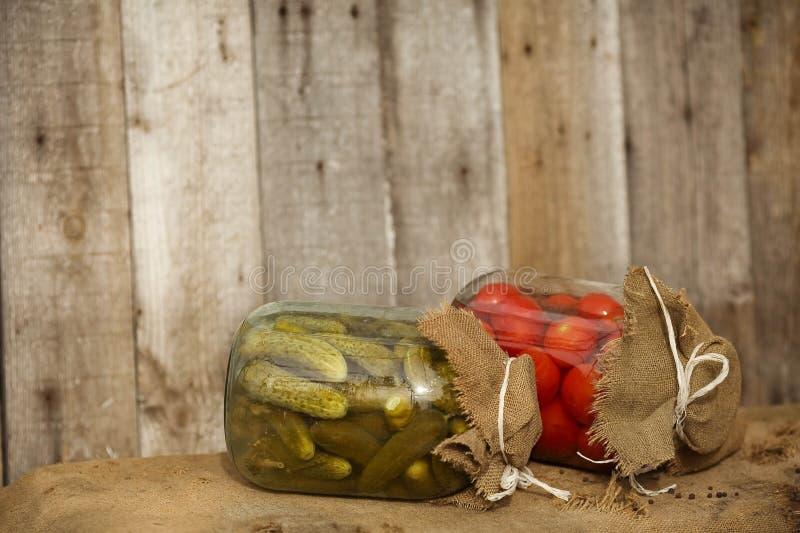 Ένα βάζο γυαλιού με τα αλατισμένες αγγούρια και τις ντομάτες στοκ φωτογραφίες