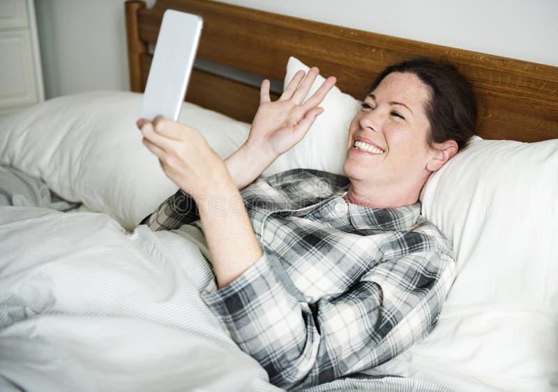 Ένα βίντεο γυναικών που καλεί μέσα το κρεβάτι στοκ φωτογραφίες