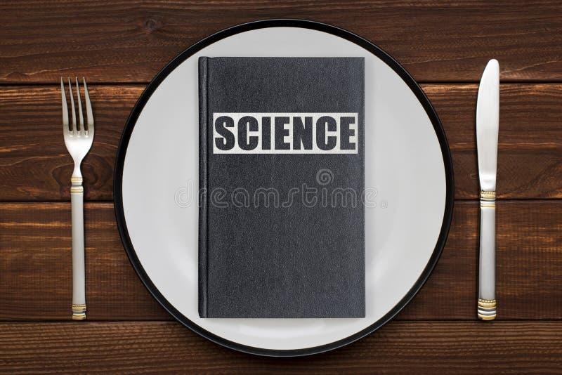 Ένα βιβλίο με την ΕΠΙΣΤΗΜΗ επιγραφής σε ένα πιάτο στοκ φωτογραφία