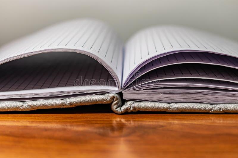 Ένα βιβλίο, ένα σημειωματάριο με ένα ελεγμένο σχέδιο σε έναν ξύλινο πίνακα σε διαφορετικό θέτει Η κάλυψη είναι γκρίζα και μαλακή  στοκ φωτογραφία
