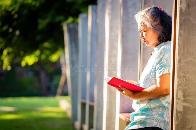 Ένα βιβλίο στον κήπο διάβαζε μια γυναίκα στοκ φωτογραφία με δικαίωμα ελεύθερης χρήσης