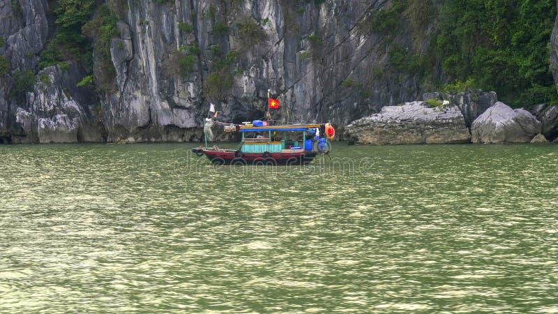Ένα βιετναμέζικο αλιευτικό σκάφος στη βάση των απότομων βράχων στον κόλπο halong στοκ φωτογραφία με δικαίωμα ελεύθερης χρήσης