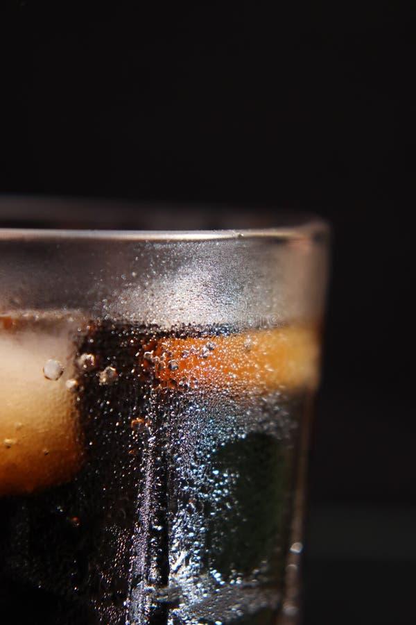 Ένα βράζοντας στον ατμό ποτήρι του κρύου thirst-quenching red-brown ποτού με τους κύβους πάγου στοκ εικόνα